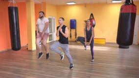 Opwarming bij de gymnastiek van de bus, een gebaard mens en meisje, die de opleiding met vechtsporten een beginnen, limbering-omh stock video