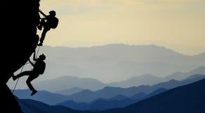 Opwindende bergbeklimming en het begeleiden vrienden stock afbeelding