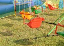 Opwindende ritten voor kinderen - schommeling, rotonde op de kettingen stock afbeeldingen