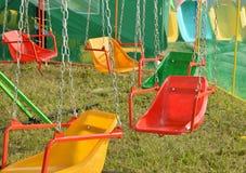 Opwindende ritten voor kinderen - schommeling, rotonde op de kettingen Royalty-vrije Stock Afbeelding
