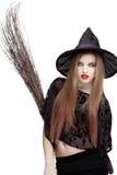 Opzichtige jonge vrouw in heksenkostuum met een bezem Stock Foto's
