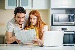 Orçamento de controlo da família, revendo suas contas bancárias usando o portátil na cozinha fotografia de stock