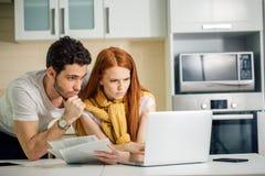 Orçamento de controlo da família, revendo suas contas bancárias usando o portátil na cozinha fotos de stock