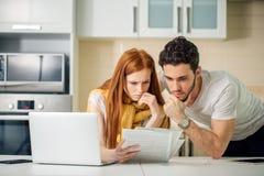 Orçamento de controlo da família, revendo suas contas bancárias usando o portátil na cozinha foto de stock