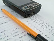 Orçamento de negócio Home com telefone móvel foto de stock royalty free