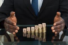Orçamento de Saving The Word do homem de negócios em moedas fotografia de stock