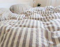 Orörda duntäcke och kuddar på en säng royaltyfri foto