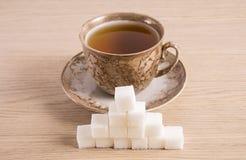 Ora della tazza di Brown con i cubi di zucchero su un fondo leggero Fotografia Stock Libera da Diritti