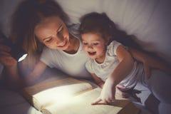 Ora di andare a letto della lettura della famiglia Libro di lettura del bambino e della mamma con un flashl Immagine Stock