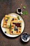 Ora di colazione Cialde casalinghe con la diffusione della banana, del mirtillo e del cioccolato su un tavolo da cucina fotografia stock libera da diritti