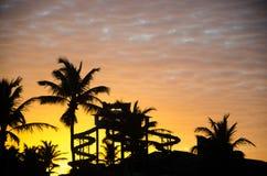Ora dorata di tramonto con le palme ed il parco acquatico fotografia stock libera da diritti