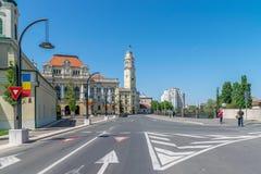 ORADEA, ROEMENIË - 28 APRIL, 2018: Mensen die op de straat met Oradea-Stadhuis op achtergrond lopen stock foto's