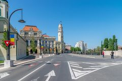 ORADEA, RUMANIA - 28 DE ABRIL DE 2018: Gente que camina en la calle con ayuntamiento Oradea en fondo fotos de archivo
