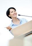 Orador de la mujer en el podium Fotos de archivo