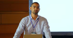 Orador masculino com o portátil que fala na fase no auditório 4k video estoque