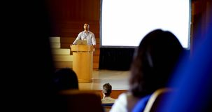 Orador masculino da misturado-raça nova com o portátil que fala na fase no auditório 4k vídeos de arquivo