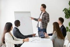 Orador masculino que faz a apresentação no flipchart durante a reunião imagens de stock