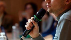 Orador na conferência que guarda o microfone filme