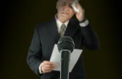 Orador público ou político nervoso que limpam o microfone da testa em f fotos de stock royalty free