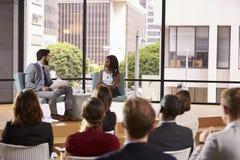 Oradores masculinos e fêmeas na frente da audiência em um seminário Imagens de Stock