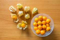 Orage gooseberries in glass bowl and some with shell on wood tab. Le, delicious fruit high in vitamins Stock Photo