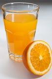 Orage-Saft in einem Glas und halb Orange dazu Stockfoto
