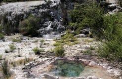 Orakei Korako暗藏的地热谷:在小瀑布的看法与蒸热的清楚的蓝色碱氯化物热量水池 免版税库存照片