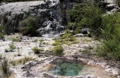 Orakei Korako hidden geothermal valley: View on cascade with steaming hot clear blue alkali chloride thermal pool royalty free stock photo
