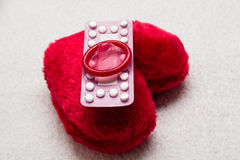 Oral contraceptive pills condom on red heart Royalty Free Stock Photography