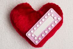 Oral contraceptive pills on red heart. Medicine contraception love and birth control. Oral contraceptive pills on red heart shaped little pillow Royalty Free Stock Photos