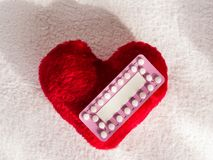 Oral contraceptive pills on red heart Royalty Free Stock Photography
