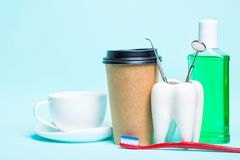 Oral dental hygiene. Healthy white tooth and dentist mirror near toothbrush, mouthwash, tea cup and plastic thermo cup of coffee. On light blue background stock photo