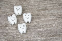 Oral health icon - cute healthy and crying decayed teeth. On wood stock images