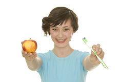 Oral hygiene. Beautiful young woman with perfect teeth and oral hygiene holding an apple and a tooth brush Stock Photos