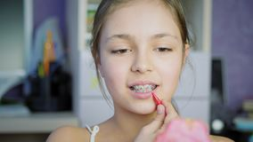 Oral hygiene for braces. Girl teenager indoors cleans braces and teeth with a special brush stock footage