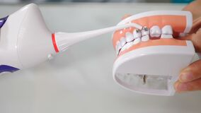 Oral hygiene for dental braces. Orthodontic Treatment concept. Teaching dental care. Dentist showing how to clean teeth