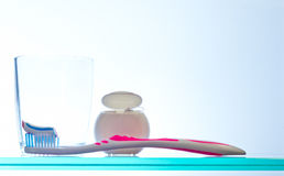 Daily oral hygiene routine. A toothbrush with striped toothpaste, dental floss and a glass tumbler all ready for cleaning teeth and gums as part of a daily oral Stock Photos