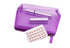 Oral ontraceptive pills, cosmetic bag, mascara and lipstick on a white background. Medicine concept, flat lay Stock Photos
