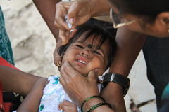 Oral Polio drops. Young child cries while taking polio drops during national polio immunization drive in asia Stock Photography