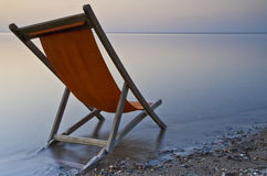 Orange. Deckchair abandoned on a beach at the end of summer Stock Images