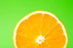 Orange. A half orange on green surface Stock Images