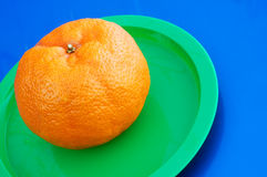 Orange. On green plate Stock Photo