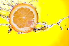 Orange. View of piece of orange getting splashed and glass of juice on back royalty free stock images
