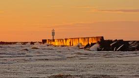 Orange Abendrot und Wellen, die gegen Wellenbrecher in der Ostsee spritzen stockbild