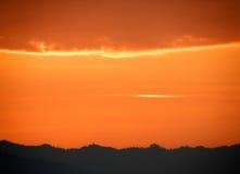 Orange Abstufung des bewölkten Himmels des Sonnenuntergangs über dem Schattenbild des Gebirgszugs Stockfotos