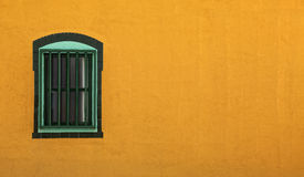 Orange adobe wall and green window Stock Photos