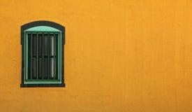 Orange adobe wall and green window Stock Photos