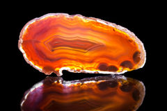 Orange agate slice, black background, healing stone and mineral Stock Photo