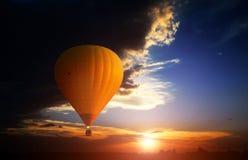 Orange air ballon flying thrue the sunset Royalty Free Stock Image