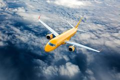 Orange airplane in flight. Orange airplane in the sky. Passenger plane flying on a high altitude above the clouds Stock Image